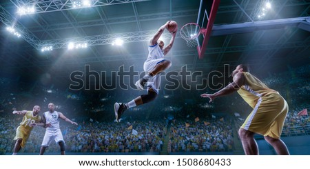 Basketball players on big professional arena during the game. Basketball player makes slam dunk. Bottom view