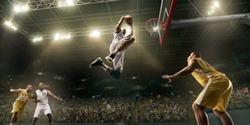Basketball players on big professional arena during the game. Basketball player makes slum dunk