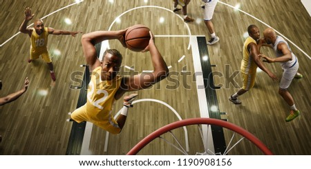 Basketball players on big professional arena during the game. Basketball player makes slum dunk. Top view through the basketball hoop