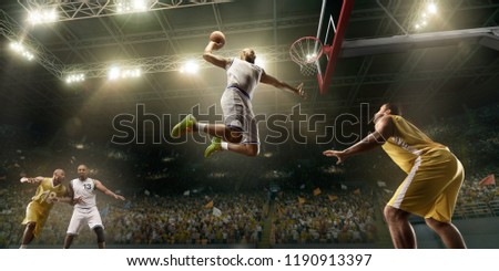 Basketball players on big professional arena during the game. Basketball player makes slum dunk. Bottom view
