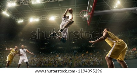 Photo of  Basketball players on big professional arena during the game. Basketball player makes slum dunk