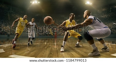 Basketball players on big professional arena during the game. Tense moment of the game. Male caucasian and black players fight for the ball