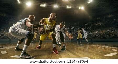Photo of  Basketball players on big professional arena during the game. Tense moment of the game. Male caucasian and black players fight for the ball
