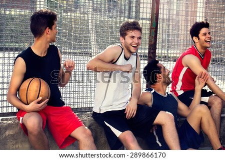 basketball players take a break sitting on a low wall