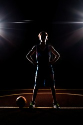 Basketball. The silhouette of a teenage Boy in blue sportswear confidently poses with his hands on his hips. The ball is on the ground. Black background with spotlights. Concept of sports games