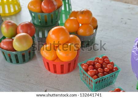 Baskets of different tomatoes for sale at a roadside fruit and vegetable market.