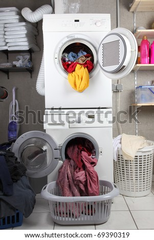 Baskets of dirty laundry in the washing room with dryer and washing machine