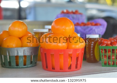 Baskets of orange tomatoes for sale at a roadside fruit and vegetable stand.