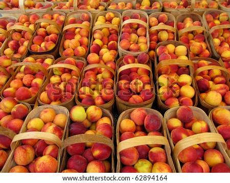 Baskets of peaches at a farmer's market.