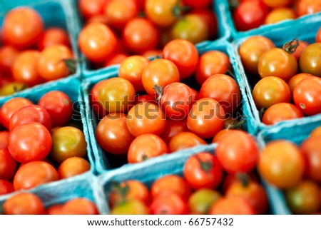 Baskets of red cherry tomatoes for sale at a farmer's market.