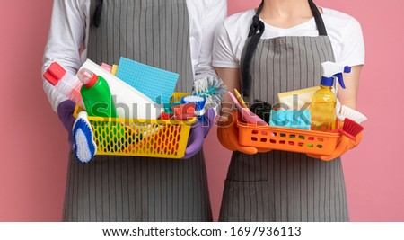 Photo of Baskets with cleaning supplies and tools in hands of unrecognizable couple standing on pink background, cropped image, panorana with free space