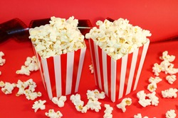 baskets with popcorn on a red background. Two baskets of popcorn. Background for cinemas. Watching a movie with popcorn