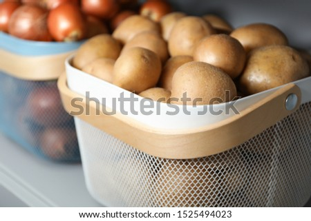 Baskets with potatoes and onions on shelf, closeup. Orderly storage