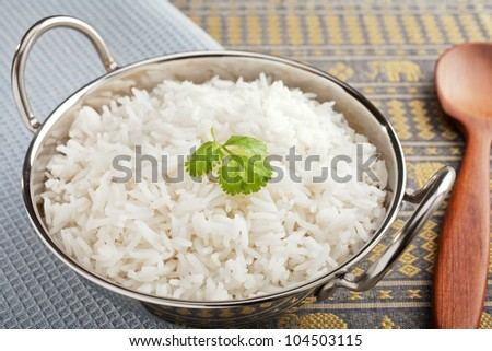 Basmati rice, perfectly cooked, in a steel karahi with a garnish or coriander.