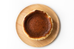 Basque burnt cheesecake in a round pound shape on a wooden tray - uncut version - top view