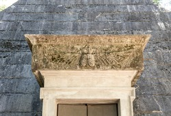Basrelief of an insect on the entrance of an old pyramid-shape ice house, building used to store ice throughout the year, in the monumental an historical Cascine park, Firenze, Tuscany region, Italy.
