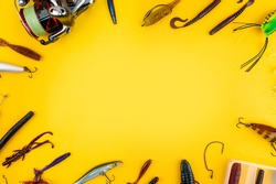 Bass fishing concept on the yellow trendy background. Flat lay style. Fishing tackle, soft silicon lures, spinner bait and wobblers.