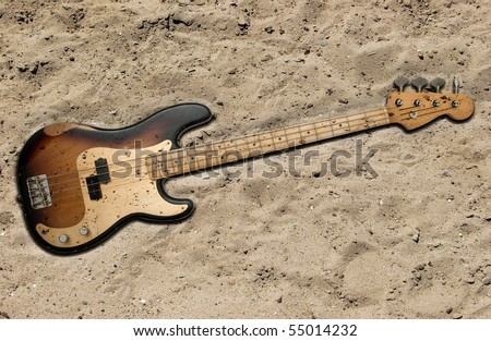 bass guitar buried in the sand