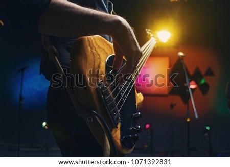 bass guitar in the hands of a musician, concept concert, learning to play the guitar, hands of a guitarist close-up #1071392831