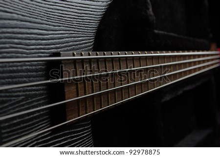 Bass guitar neck on the black background