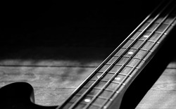 Bass guitar on wooden floor in black and white