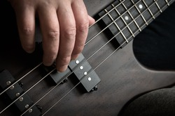 Bass guitar player hand closeup, lesson and practice theme. Playing rock on bass electric guitar, live music and skill concept. Close view of guitarist fingers and bass instrument strings.