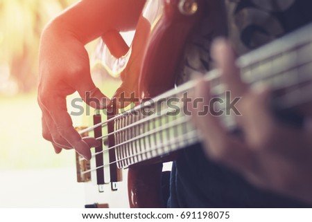 Bass guitar player or guitarist playing music instrument (focus on hand)