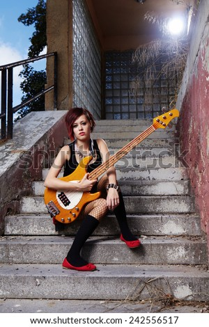 Bass guitar woman player posing on street city location for stylish musician portraits