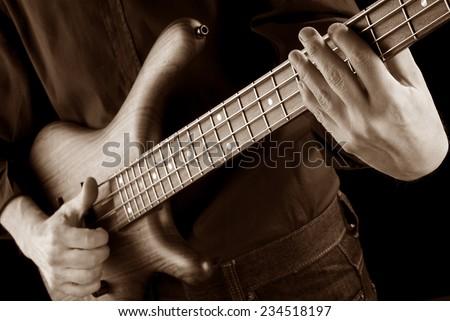 bassist playing funk slap on bass guitar, sepia image