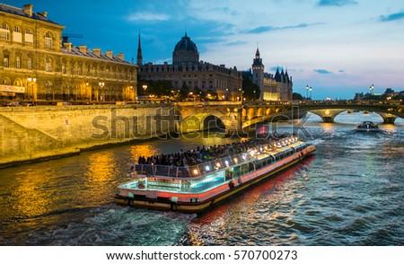 Bateau Mouche cruising on Seine river at sunset, Paris.