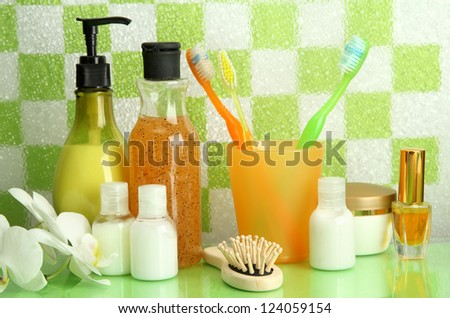 Bath accessories on shelf in bathroom on green tile wall background