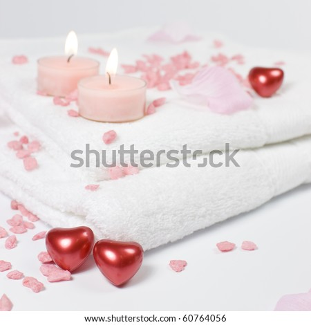 Bath and spa Valentine theme with white towels, pink bath stones - salt and red hearts.