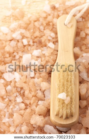 Bath brush on heap of peach-colored bath salt.