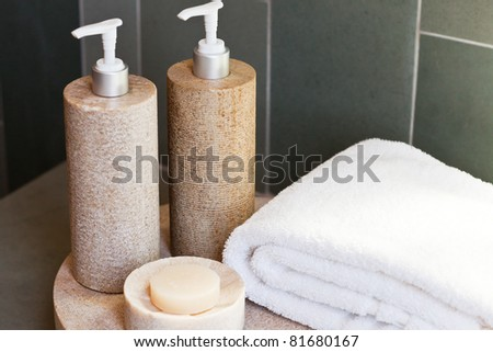 bath dispensers, soap and white towel on the tray