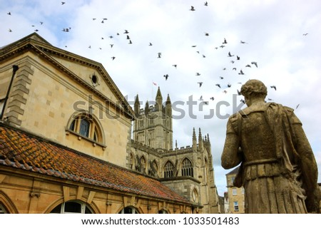 Bath (England, UK) Stone statue of the roman in Antique Roman Baths complex, flying birds in sky and Abbey Cathedral at background. City of Bath is a UNESCO World Heritage Site.