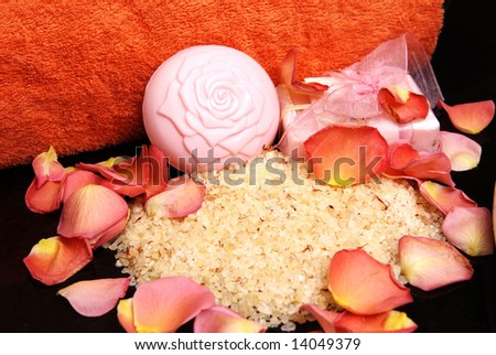 Bath salt and soap with a pink ribbon, with rose petals and bright orange towel laying on black granite