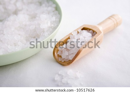 Bath salts in a green bowl with wooden scoop - stock photo