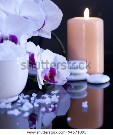 Bath sea salt with candle and orchid on the black background.