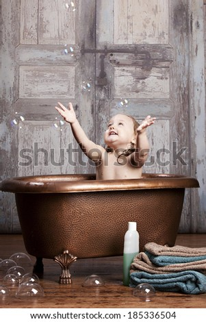 Bath time fun.  Adorable toddler playing in the tub.  Room for your text.