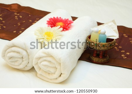 bath towels rolled with flower on bed