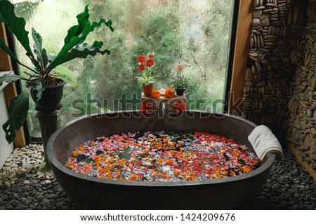 Bath tub filling with water with flowers and lemon slices. Organic spa relaxation in luxury Bali outdoor bathroom