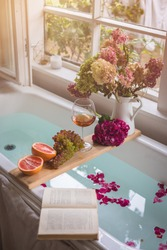 Bath tub with flower petals, grapefruit slices, bunch of grapes, a glass of wine, opened book and hydrangea bouquet. Organic spa relaxation preparation