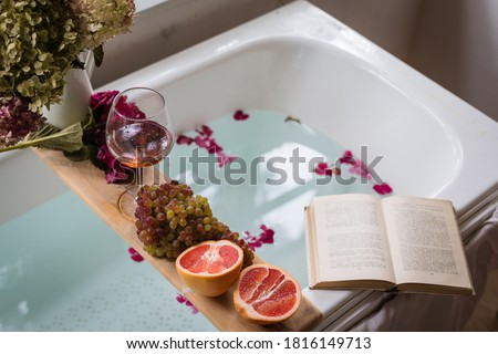 Bath tub with flower petals, grapefruit slices, bunch of grapes, a glass of wine, opened book and hydrangea bouquet. Organic spa relaxation preparation Foto stock ©