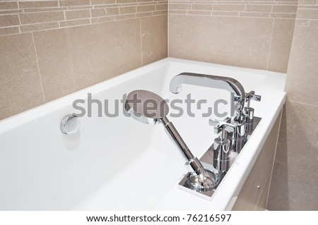 Bath Tub With Modern Fixtures And Shower Attachment Stock Photo