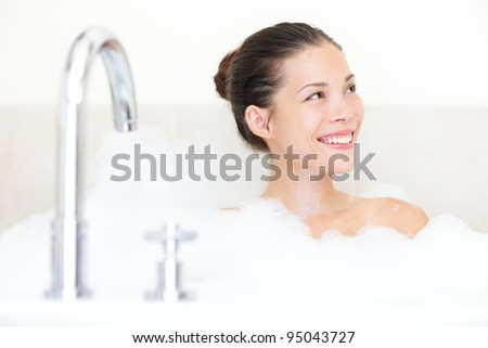 Bath woman enjoying bathtub with bath foam smiling happy. Mixed race Asian / Caucasian female model in bathroom.