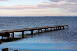 Bathing jetty on rocky beach during winter in the seaside fishing village of Kattvik, Bastad situated on the Swedish west coast.