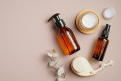 Bathroom cosmetics and accessories on brown background. Flat lay, top view. Pump bottle, cosmetic spray lotion, candles, body clean brush, eucalyptus leaf.
