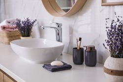 Bathroom counter with vessel sink, accessories and flowers. Interior design