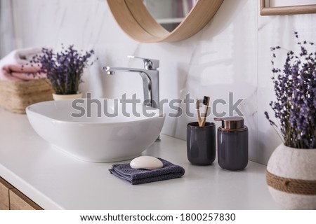 Bathroom counter with vessel sink, accessories and flowers. Interior design Foto d'archivio ©