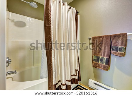 Bathroom detail. Tub and shower combo with white and brown curtain, green walls and towels hanging on a rail. Northwest, USA #520161316